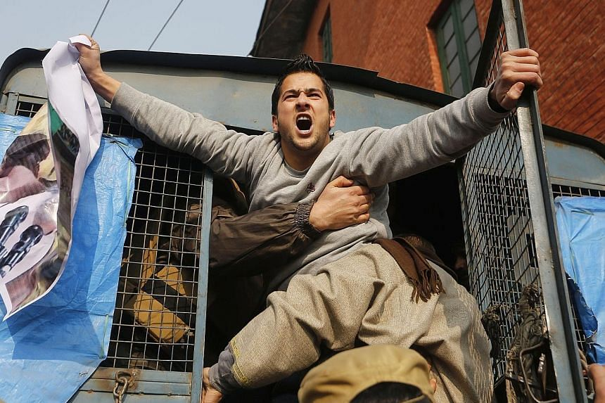 A Kashmiri Shi'ite Muslim shouting slogans while being removed by Indian police during a protest in Srinagar, in Indian Kashmir, yesterday over Saudi Arabia's execution of Shi'ite cleric Nimr al-Nimr.