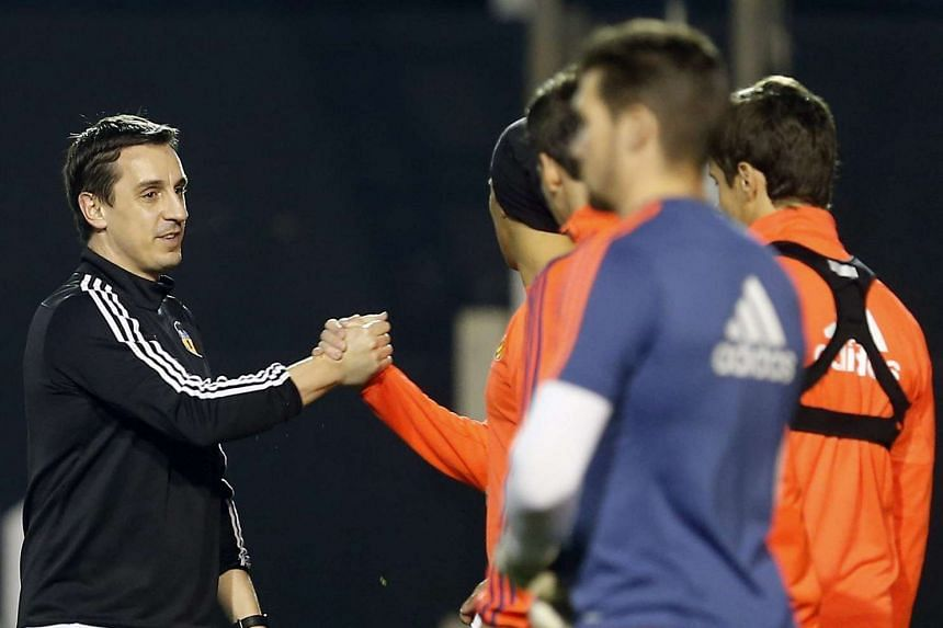 Valencia FC's head coach, Gary Neville (left) greets his players during a training session.