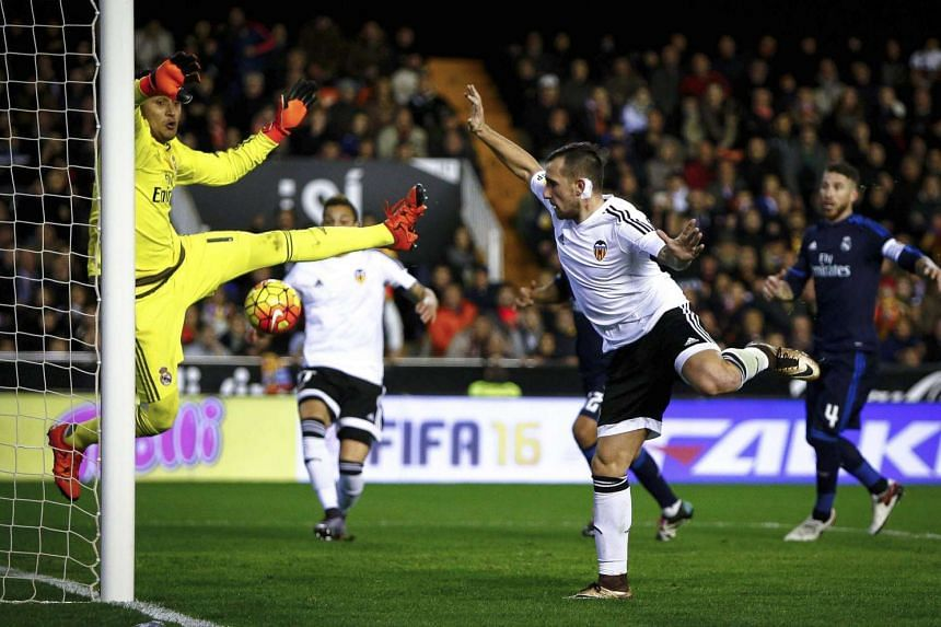 Valencia CF's striker Paco Alcacer (centre) scores against Real Madrid's Costa Rican goal keeper Keylor Navas (left) on Sunday.