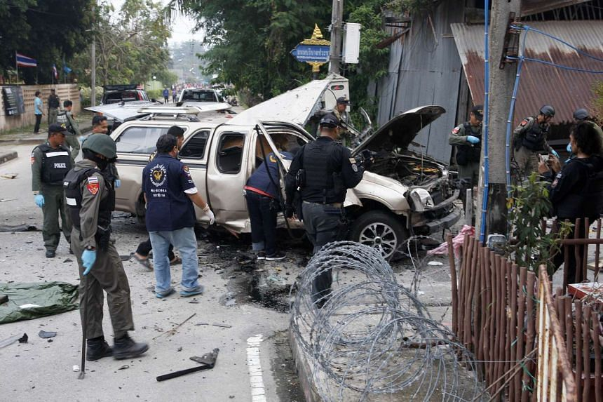 Members of a bomb squad unit inspecting the scene following a blast in southern Thailand.