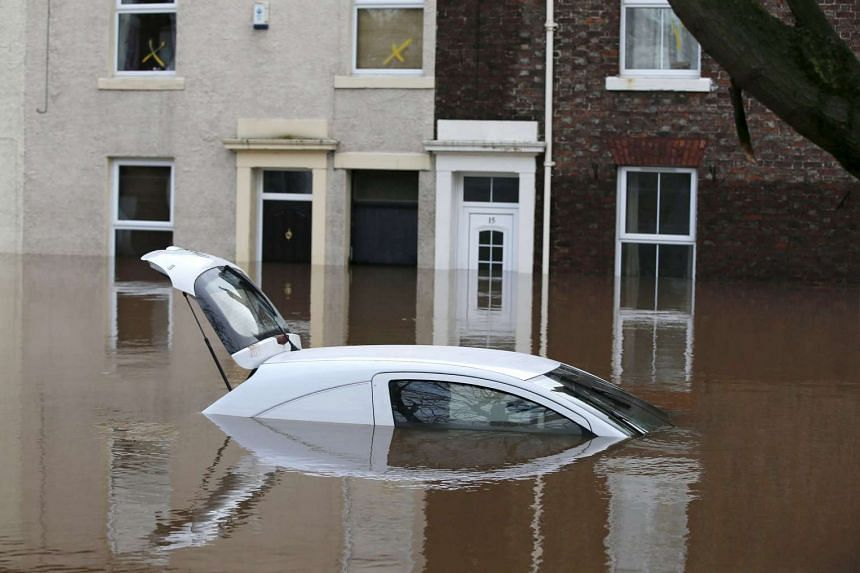 A car is submerged under flood waters in the city centre of Carlisle, north west England, on Dec 7, 2015.