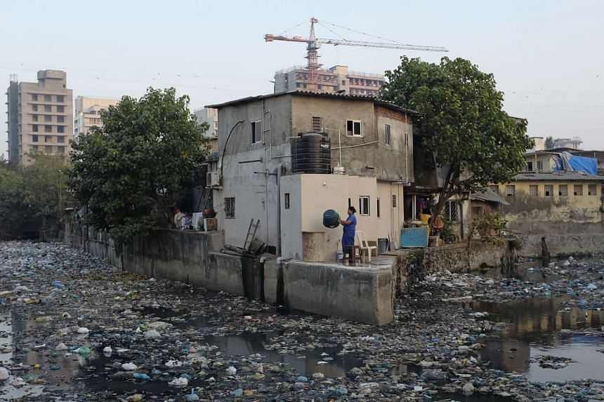 A woman washes her clothes in a canal filled with rubbish in a slum in Mumbai, India.
