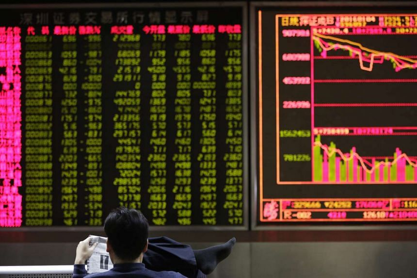 A man reading a newspaper at a stock brokerage house in Beijing, China, on Jan 4, 2016.