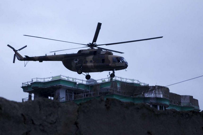 An Afghan National Army helicopter drops commandos on the roof of a building during an operation near the Indian consulate in Mazar-i-Sharif, Afghanistan, on Jan 4, 2016.