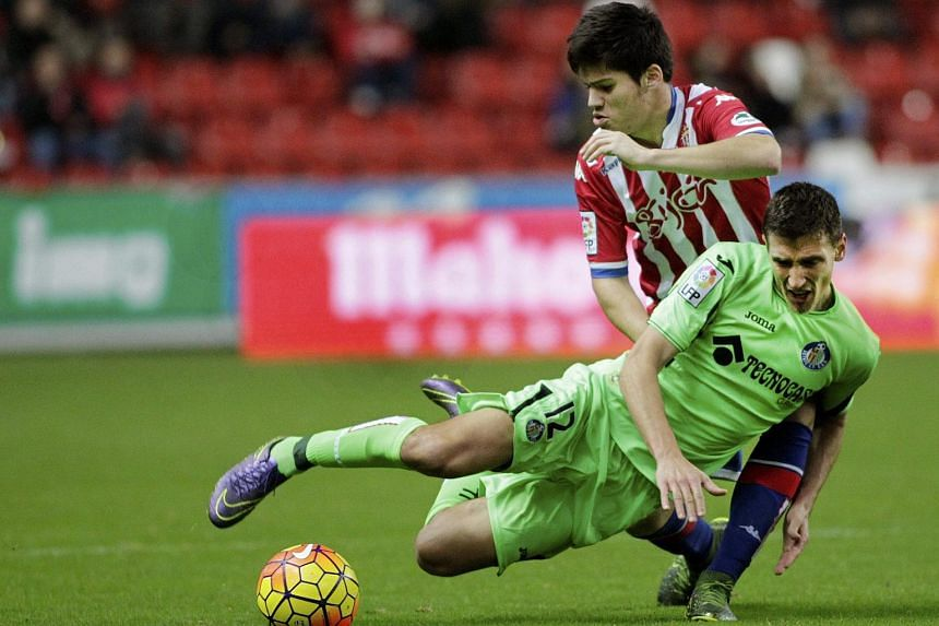 Sporting Gijon's defender Jorge Mere (back) duelling for the ball with Getafe's player Scepovic on Dec 4, 2015.