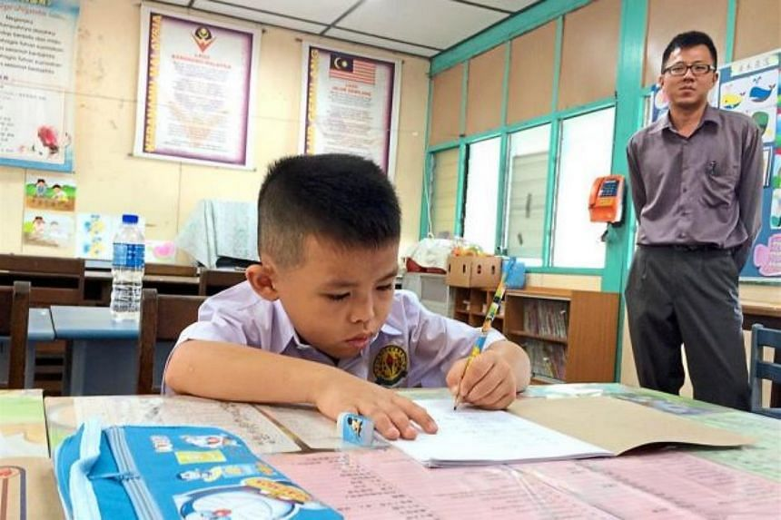 Oon Sheng Juin learning to write on his first day as his teacher Tan Boon Lin looks on.