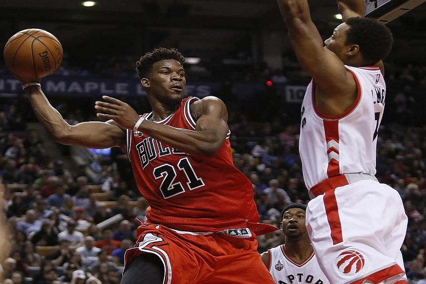 Bulls guard Jimmy Butler looking to pass the ball as Raptors guard Kyle Lowry defends at the Air Canada Centre. Chicago beat Toronto 115-113 after trailing by as many as 15 points, and Butler's 40 points in the second half beat Michael Jordan's 39-po