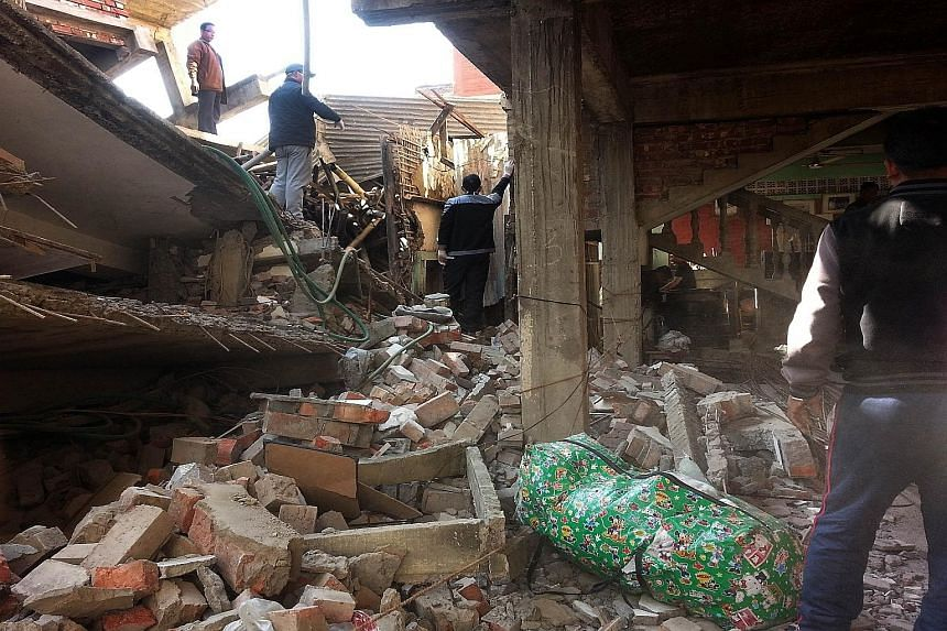 Residents inspecting the wreckage of a building in Imphal yesterday, after a 6.7-magnitude earthquake struck north-east India near the country's borders with Myanmar and Bangladesh.