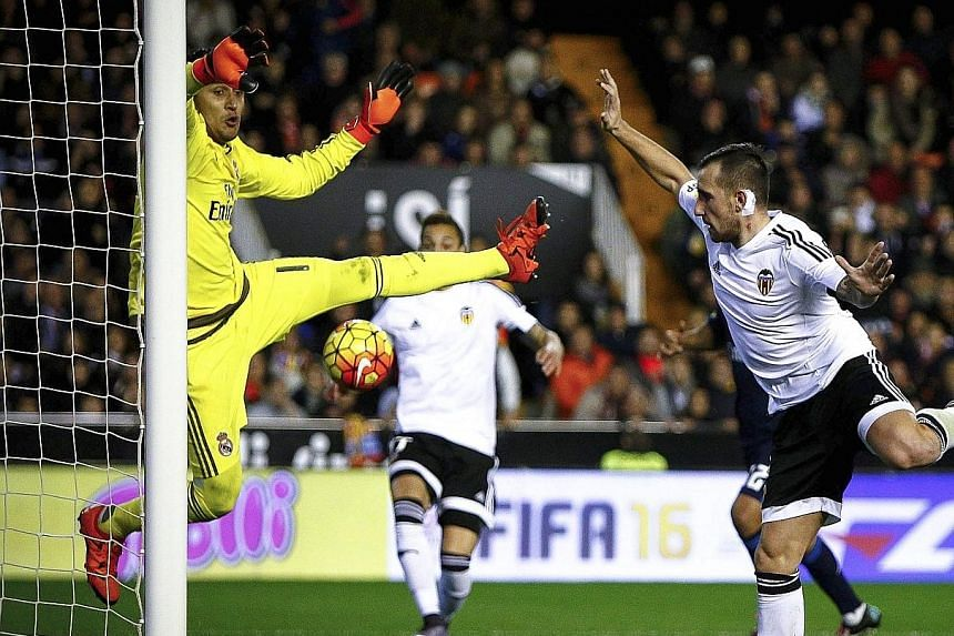 Valencia striker Paco Alcacer scoring his team's first equaliser against Real Madrid's goalkeeper Keylor Navas at the Mestalla. The match, which both managers badly needed to win, ended 2-2.