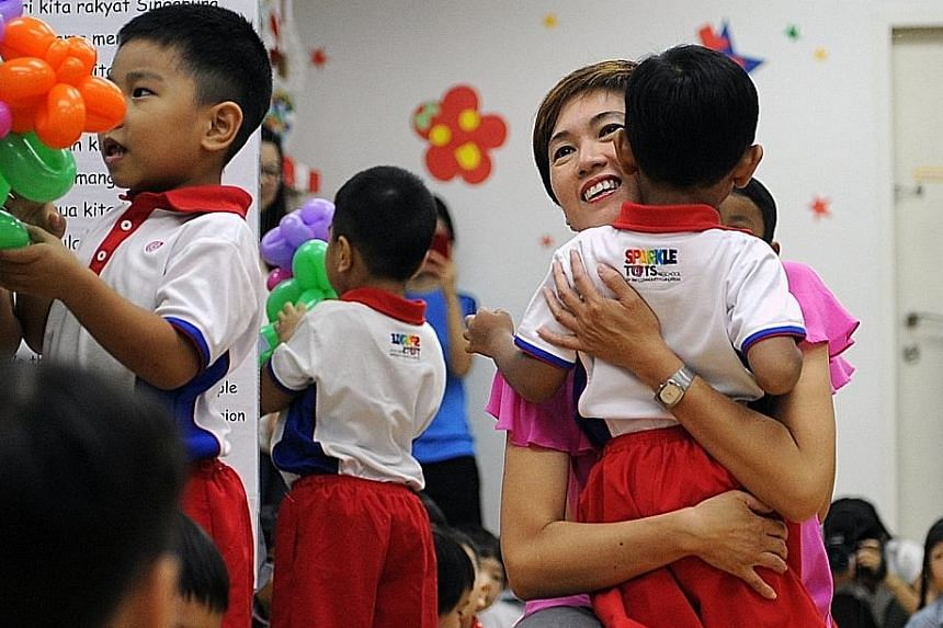 Mrs Teo welcoming children back to school at the PAP Community Foundation Sparkletots Childcare in Bishan yesterday. The Senior Minister of State said she will focus on ensuring a conducive environment for couples to start a family, among other prior