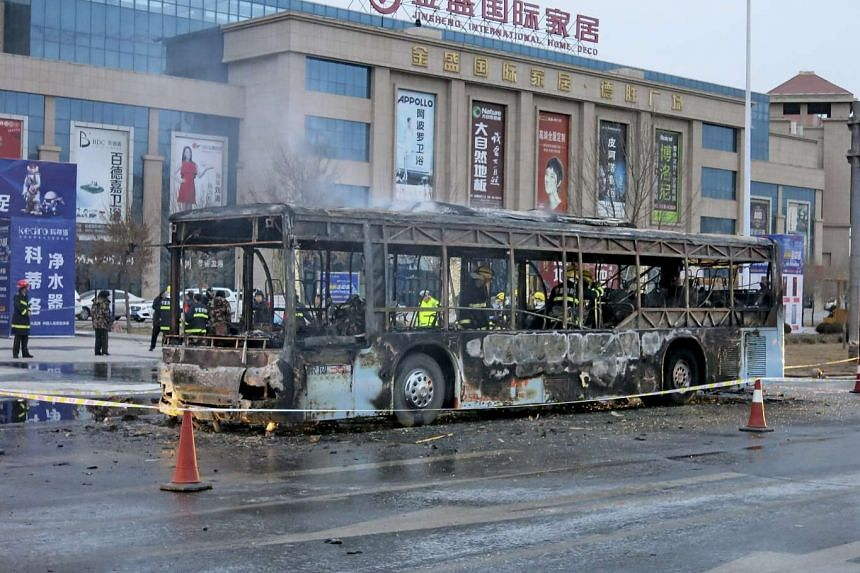 Firefighters working inside a burnt bus after a fire on a street in Yinchuan, Ningxia Hui Autonomous Region, China on Jan 5, 2016.