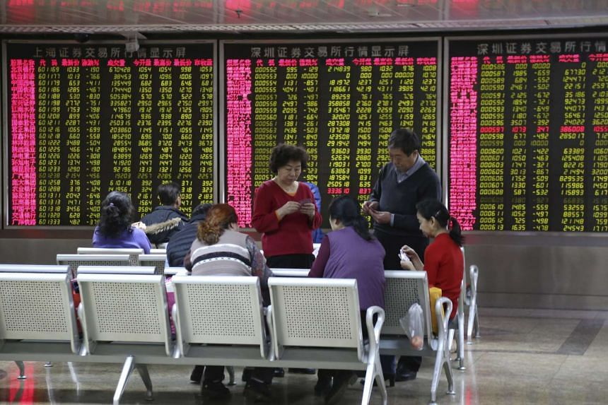 People playing cards in front of an electronic board showing stock information at a brokerage house in Beijing, China, on Jan 4, 2016.
