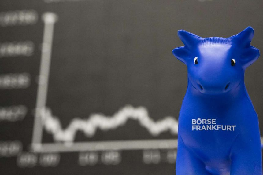 A toy bull sits in front of the DAX Index curve at the Frankfurt Stock Exchange in Frankfurt, Germany, on Monday.