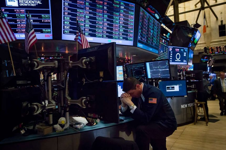 A trader bows his head while working on the floor of the New York Stock Exchange (NYSE) on Monday.