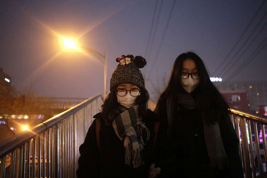 People wearing protective masks on a heavily polluted day in Beijing on Jan 3, 2016.