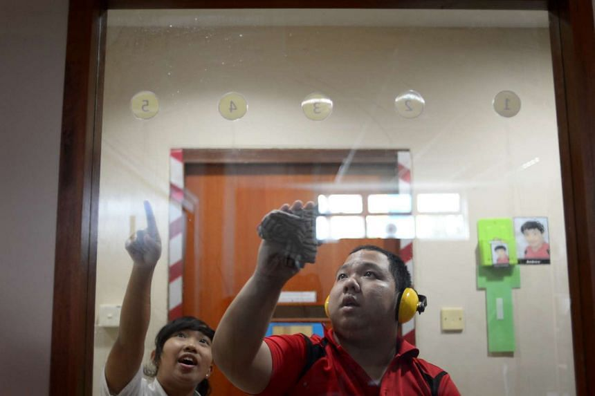 Autistic adult Lu Yong Cheng (left) cleaning windows with the help of student volunteer Nur Syakilah Roslah from ITE College Central at the Eden Centre For Adults on on Feb 20, 2013.