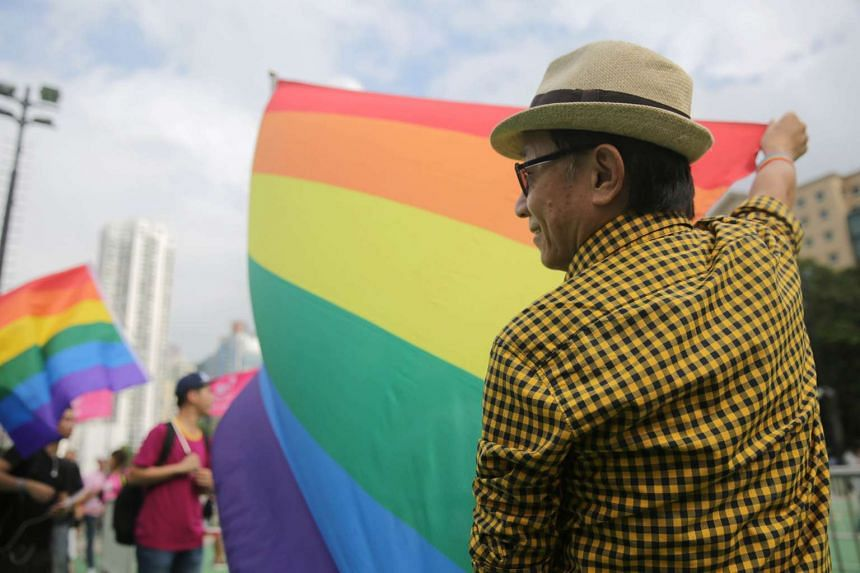 A man holds a rainbow flag while taking part in an LGBT parade in Hong Kong, China.