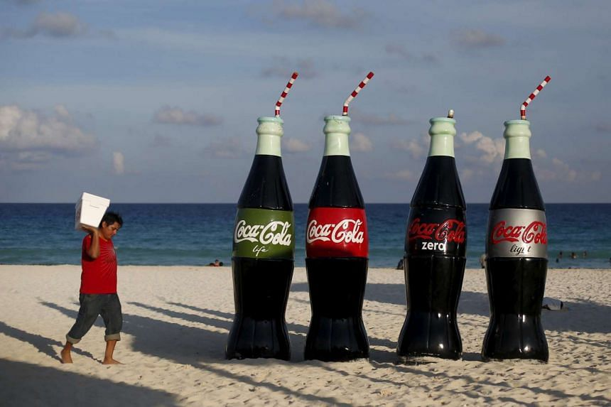 A man carries a cooler as he passes giant bottles of Coca Cola on a beach in Cancun, on Oct 13, 2015.