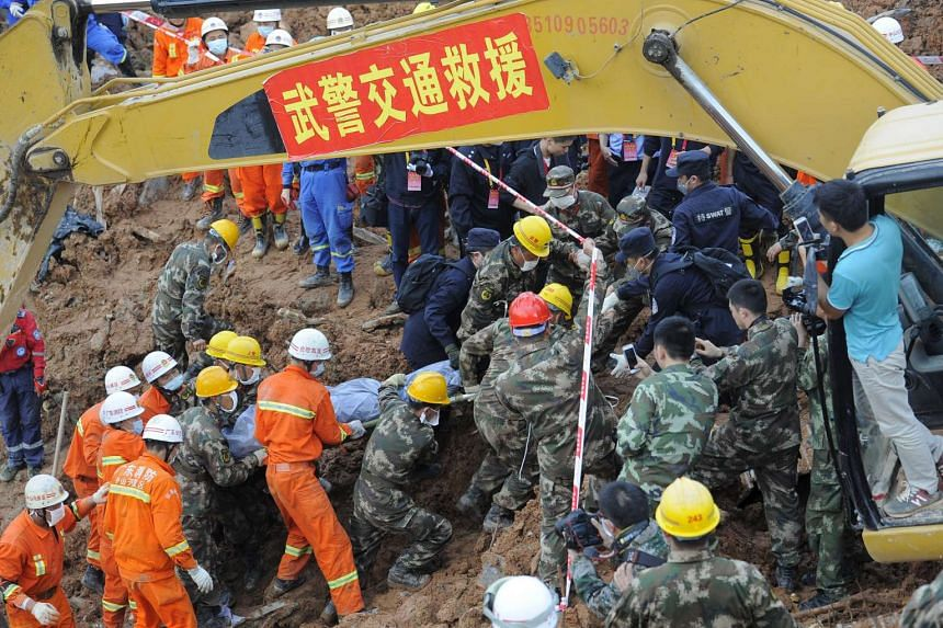 Rescuers carrying the body of a victim in the aftermath of a landslide in Shenzhen, on Dec 23, 2015.