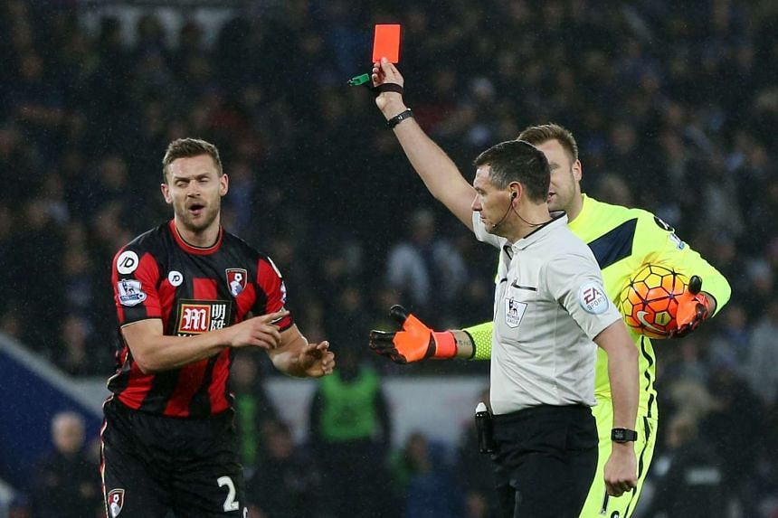 Referee Andre Marriner shows a red card to Bournemouth's Simon Francis.