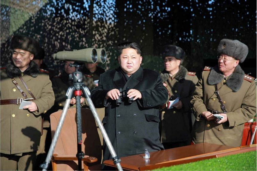 North Korea's Kim Jong Un (centre) watching a firing contest for military artillery units in a photo released on Jan 5.