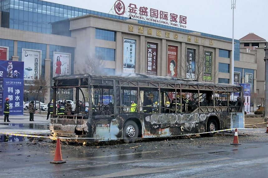 Firefighters inside the burnt bus on a street in China's Ningxia Hui Autonomous Region on Jan 5, 2016.