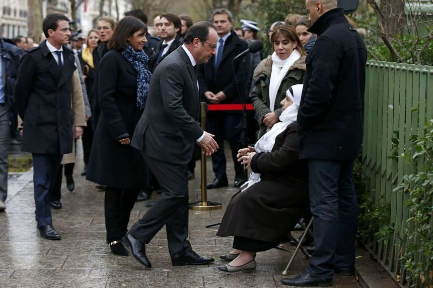 French President Francois Hollande (centre) and Paris Mayor Anne Hidalgo (second, left) greeting the mother of Ahmed Merabet, the policeman who was killed during the last year's January attack, on Jan 5, 2016.