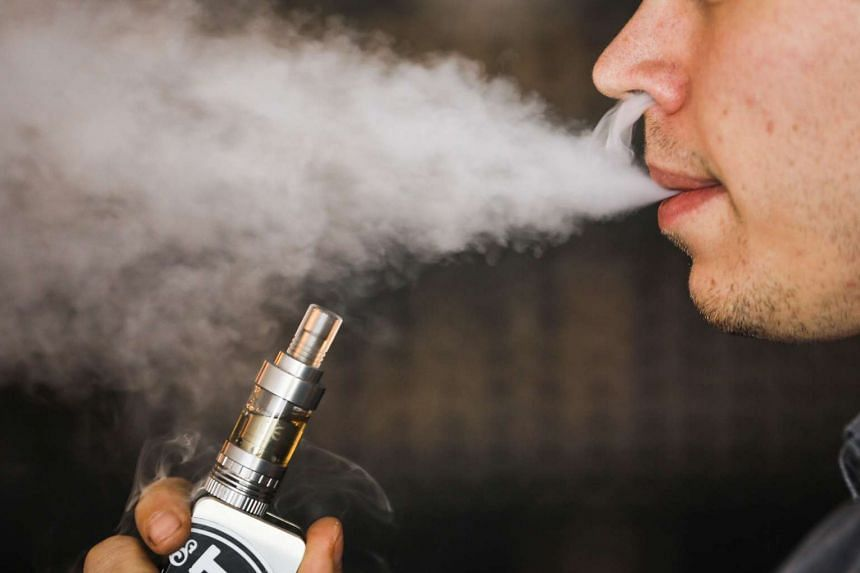 A man smokes an electronic cigarette vaporizer, also known as an e-cigarette, in Toronto, in this Aug 7, 2015, file photo. E-cigarette companies are reaching about seven in 10 US middle- and high-school students with advertisements.
