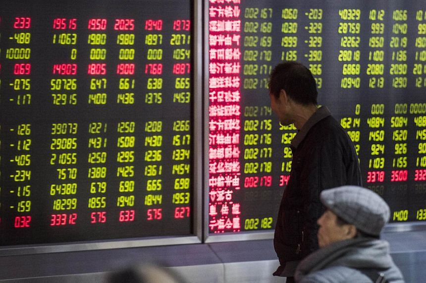 An investor looking at screens showing stock market movements in Beijing on Jan 5, 2016.