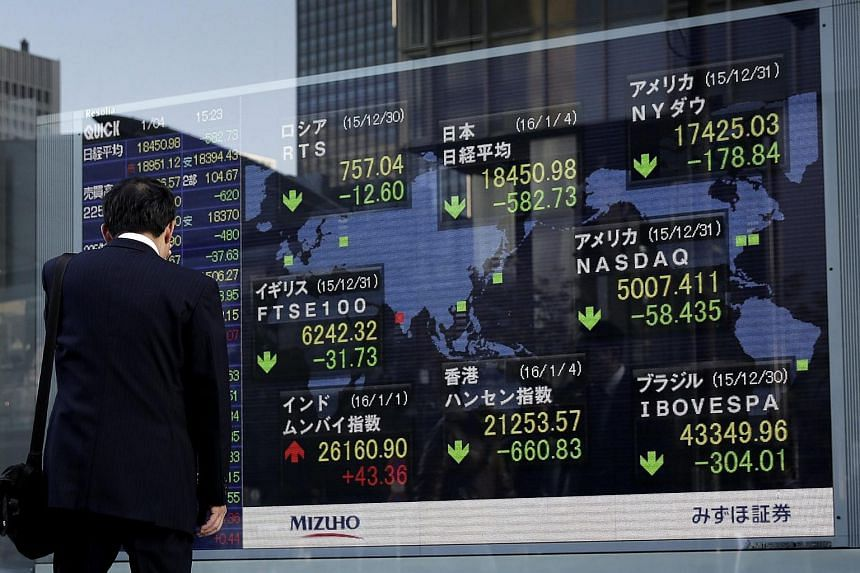 A pedestrian looking at a stock market indicator board displaying the closing information of Tokyo's Nikkei Stock Average.