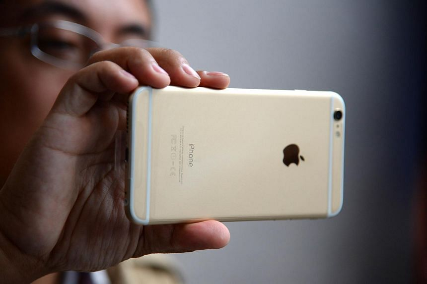 A man looking at his iPhone 6 Plus.