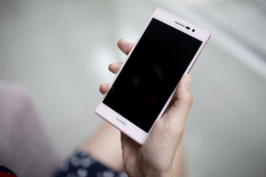 A woman holding a Huawei Technologies Ascend P7 smartphone.