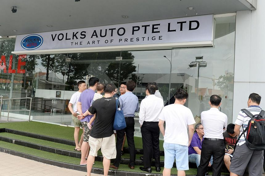 People gathering outside Volks Auto. Former employee Koh Chek Seng was charged with conspiring to commit criminal breach of trust.