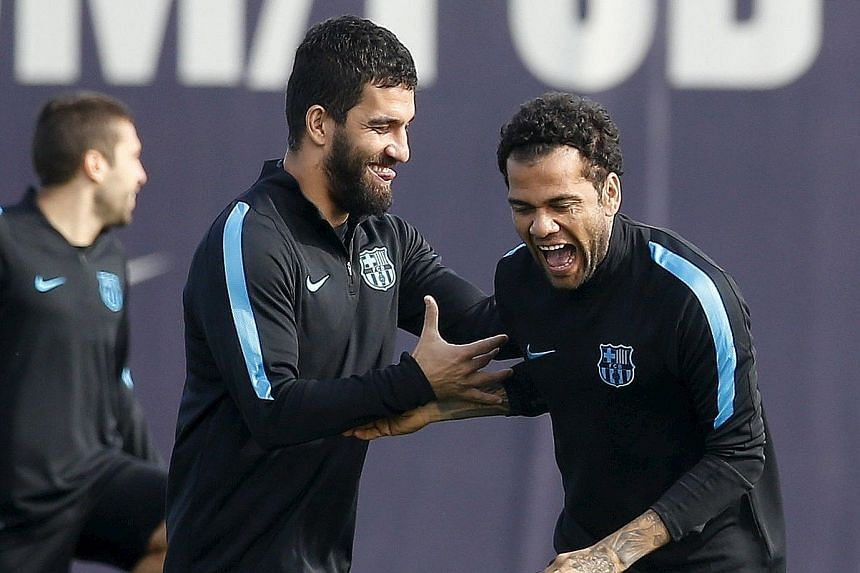Barcelona's Dani Alves (right) joking with Arda Turan during a training session. Turan will be hoping to make his debut against Espanyol today.