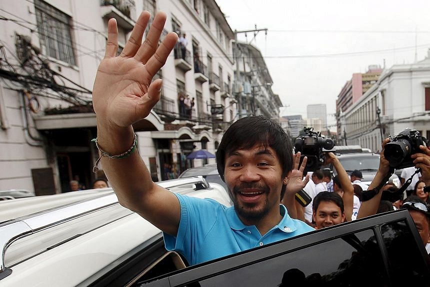 Manny Pacquiao waving after filing his certificate of candidacy for senator at the Commission on Elections in Manila for May's national polls.