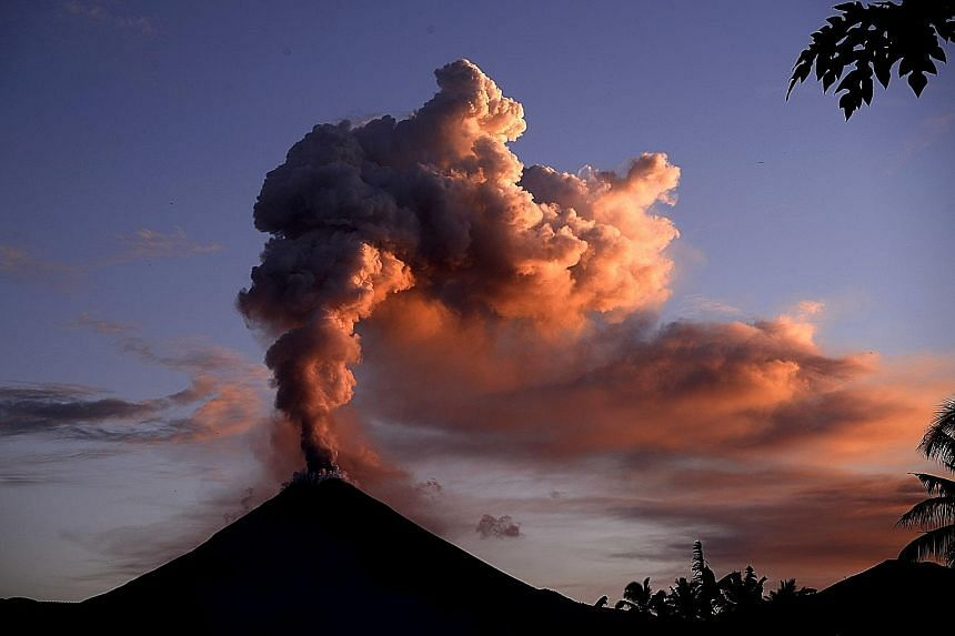 Mount Soputan spewing ash into the air during an eruption seen from Silian village, in Indonesia's province of North Sulawesi, yesterday. The volcano started erupting on Monday night, according to the country's National Disaster Mitigation Agency, sp