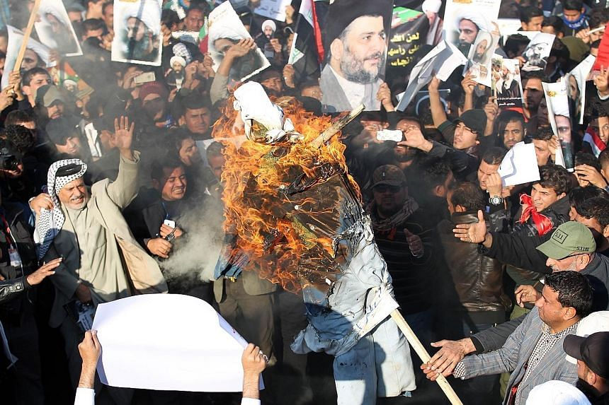 (Left) Iraqi protesters burning an effigy of a member of the Saudi ruling family during a demonstration in Baghdad on Monday against Saudi Arabia's execution of Shi'ite cleric Nimr al-Nimr. (Above) In Bahrain, a woman holding a poster of Nimr during