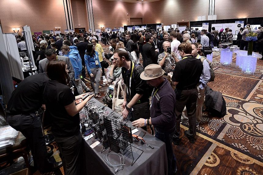 Left: Members of the media trying new products at a Consumer Electronics Show event at the Mandalay Bay Resort and Casino in Las Vegas on Monday. Above: A Samsung executive using the Samsung Gear S2 smartwatch to control a new Samsung TV. Other featu
