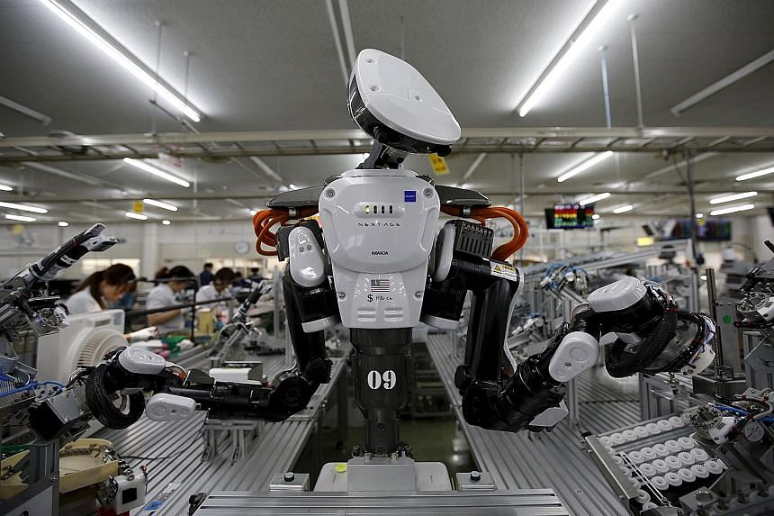 A robot on the assembly line of Japanese company Glory Ltd, which manufactures automatic change dispensers. Researchers say robots could fill the jobs done by half of Japan's workers within 20 years.