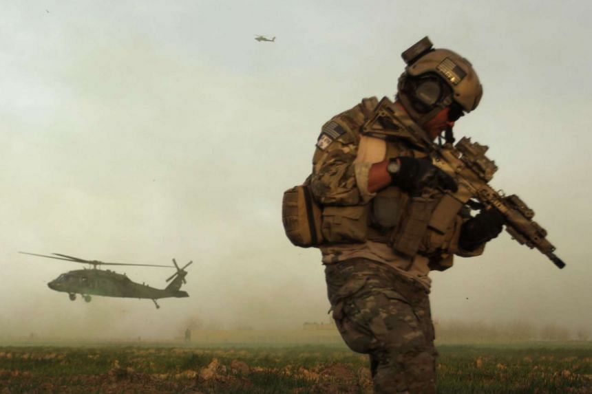 A US army special forces soldier takes cover as a Blackhawk helicopter lands in Marjah, in a file photo.