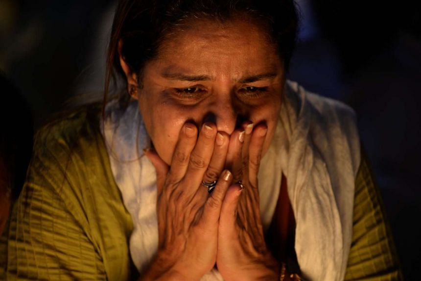 An Indian mourner reacts during a vigil on Wednesday for Indian soldiers killed in an attack on an air force base in Mumbai.
