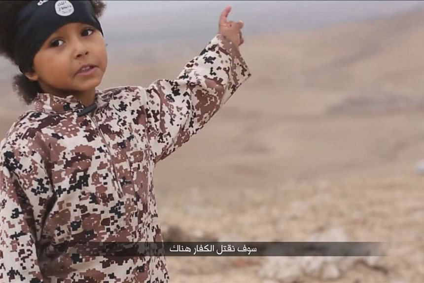 The ISIS video featured a masked militant and a young boy in military fatigues (above) who both spoke with a British accent. British media speculated that the militant might be Siddhartha Dhar, a high-profile Islamist. In this photo of a protest outs
