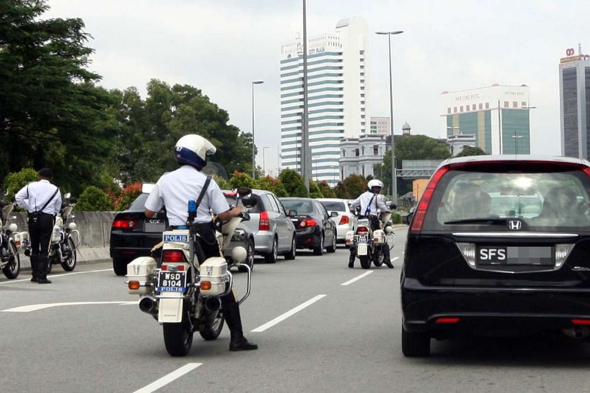 Malaysian police checking Singapore cars in an operation to nab those with outstanding traffic fines in June 2015.