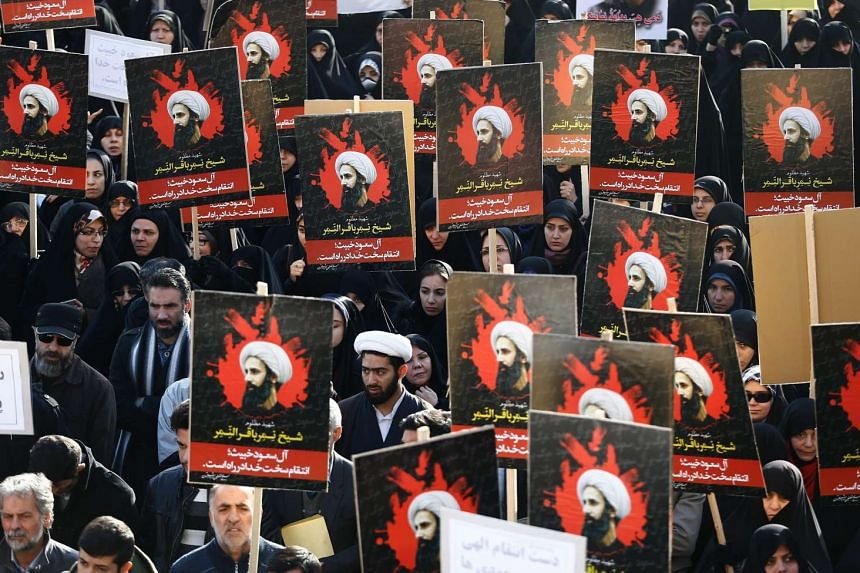 Iranian protesters hold posters of Shi'ite cleric Nimr al-Nimr during an anti-Saudi Arabia demonstration in Teheran on Jan 3, 2016.