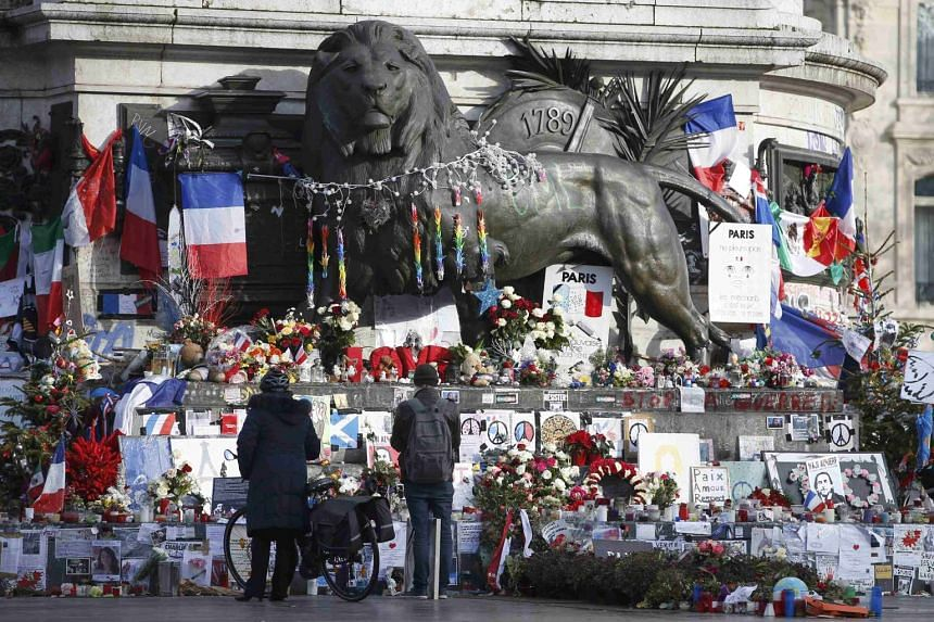 People look at flowers and messages to pay tribute to the victims of last year's January and November shooting attacks near the statue at the Place de la Republique in Paris, France.