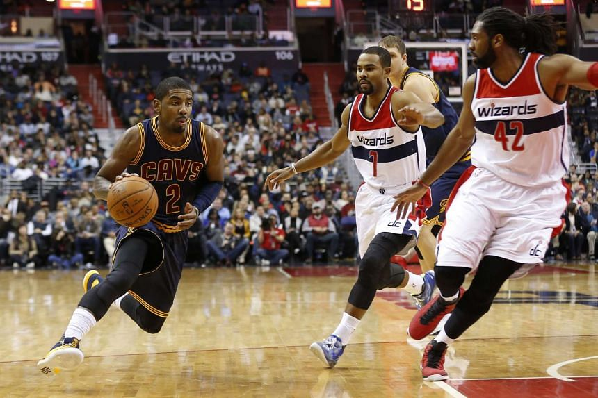 Cleveland Cavaliers guard Kyrie Irving (left) dribbles the ball against Washington Wizards guard Ramon Sessions (second from right) and centre Nene on Jan 6, 2016.