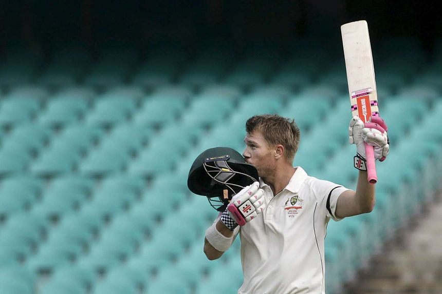 David Warner kisses his helmet in celebration after scoring a century against the West Indies.