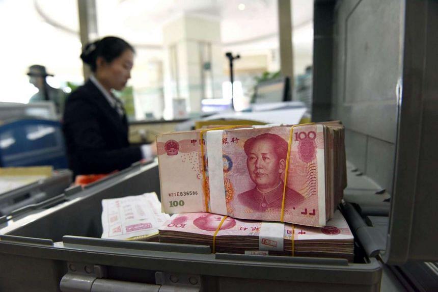 An employee counting 100-yuan (S$22) banknotes at a bank in Lianyungang, Jiangsu province, on Jan 7, 2016.