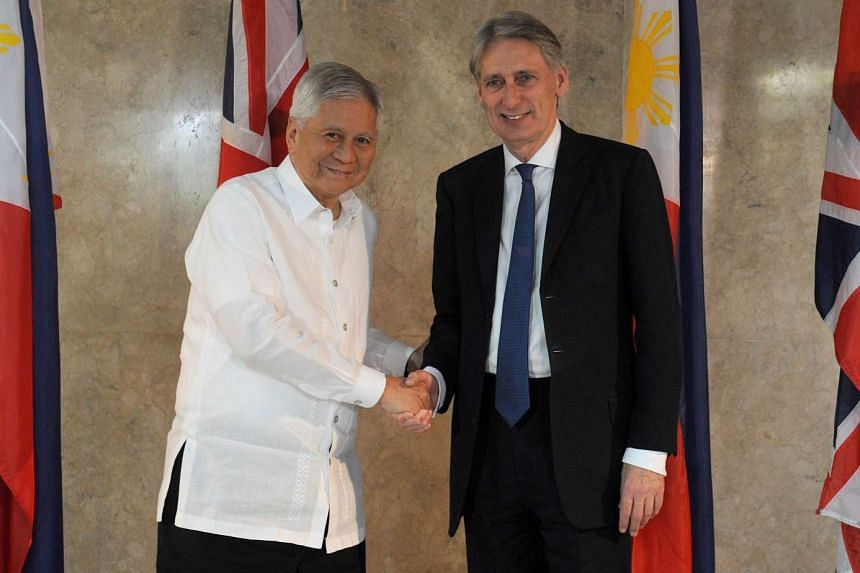 Philippine Foreign Secretary Albert del Rosario (left) shakes hands with his British counterpart Philip Hammond during a visit to the Philippine foreign ministry headquarters in Manila on Jan 7, 2016.