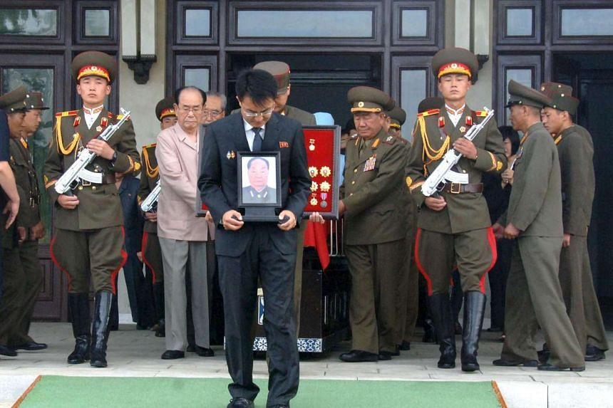A man carries a portrait of Jon Pyong Ho during his state funeral in Pyeongyang on Jul 10, 2014.